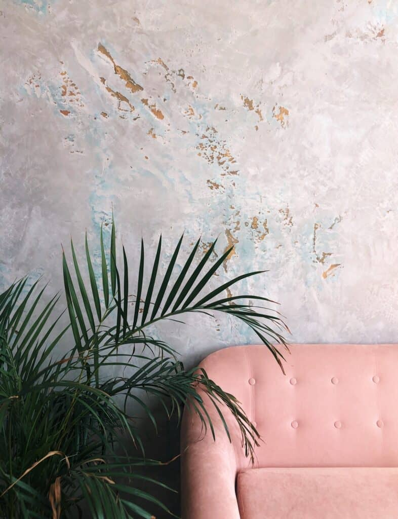 Part of home interior. Pink sofa and green leave