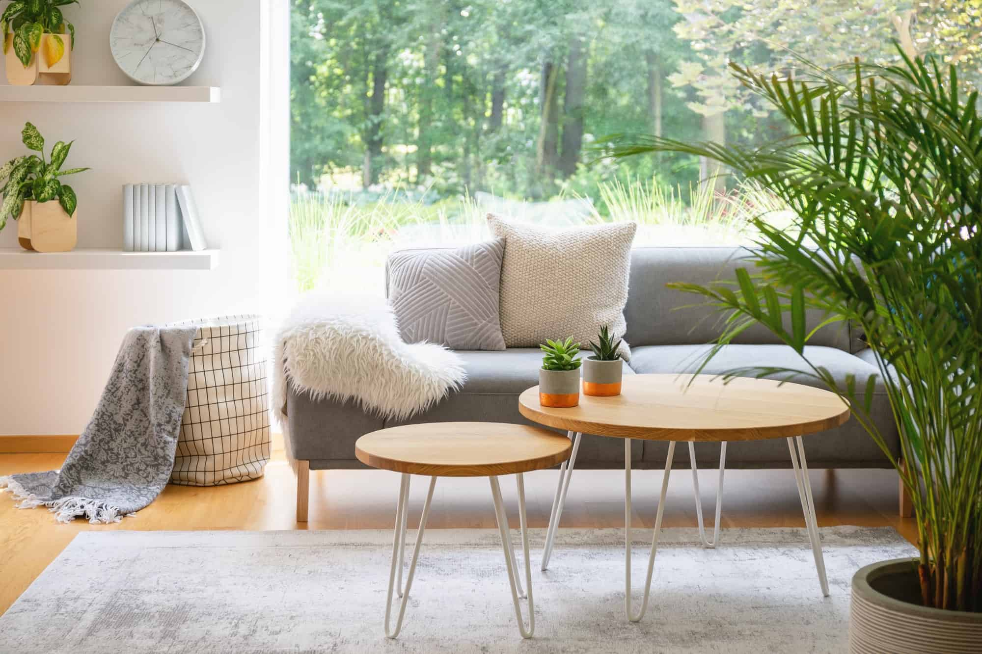 Wooden tables in front of grey sofa with cushions in scandi livi
