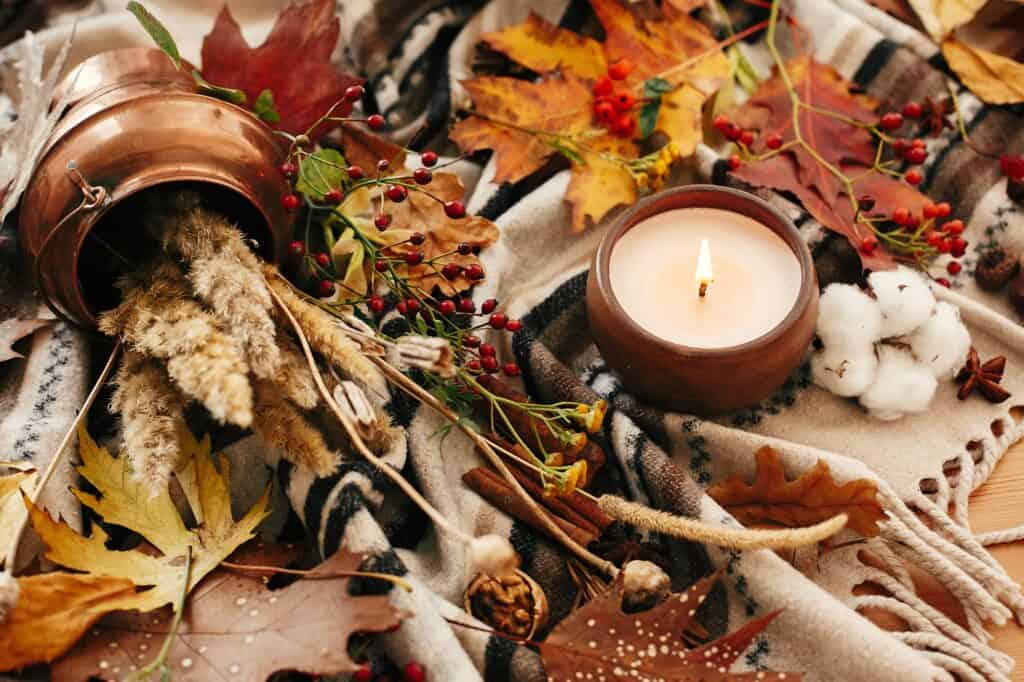 Hygge lifestyle, cozy autumn mood. Hello autumn. Candle with berries, fall leaves