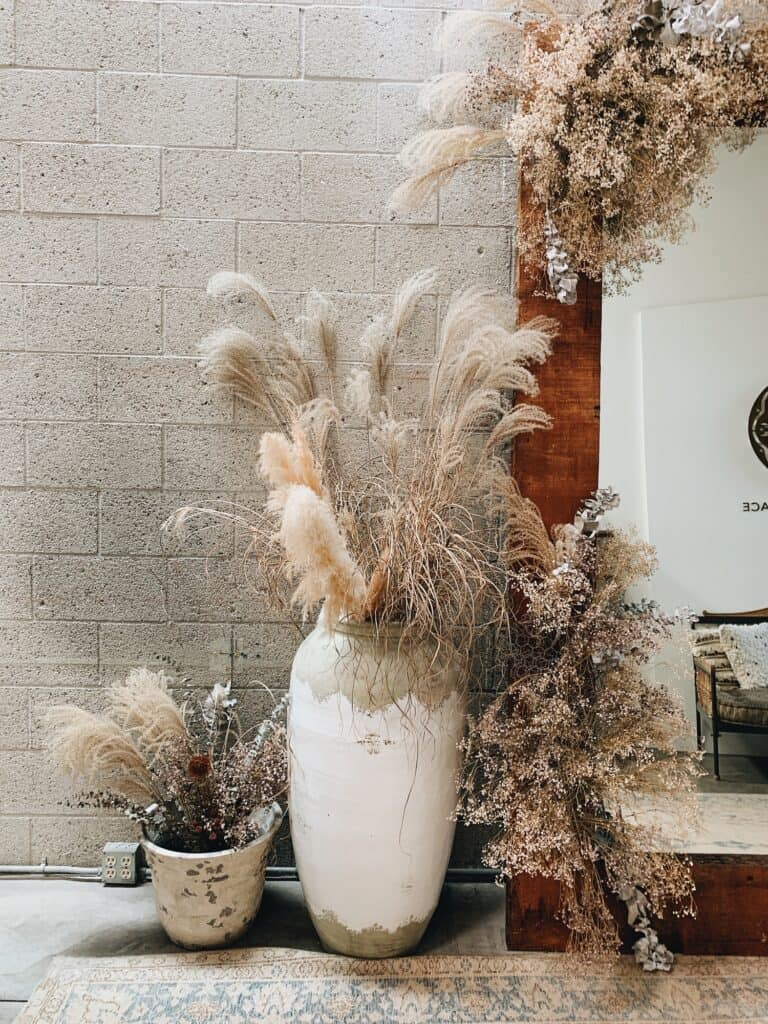 Beautiful decor with plumes and dried grasses are arranged in an elegant bridal store