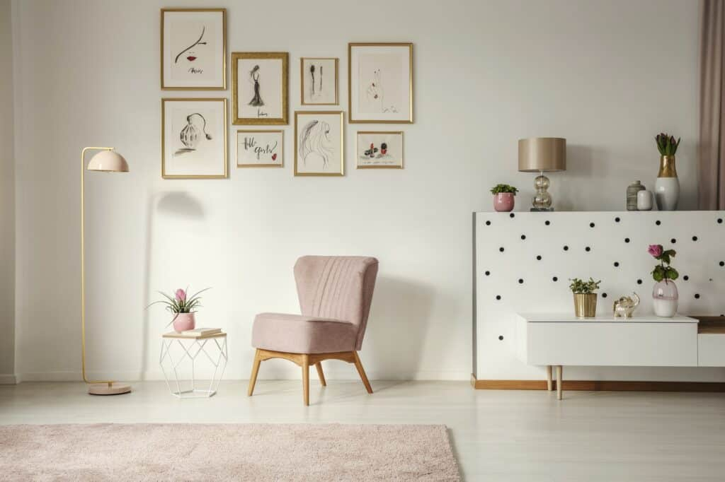 Old-fashioned armchair, pastel pink floor lamp and stylish, gold