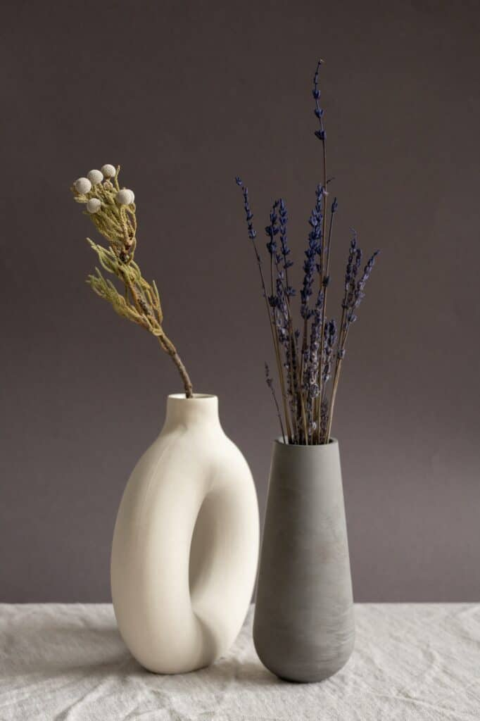 Two handmade ceramic vases of white and black color with dried flowers inside