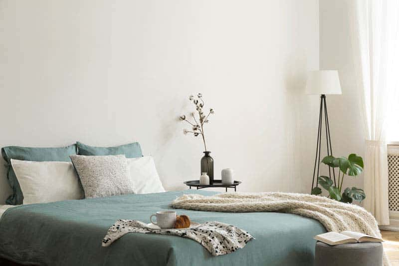 Bedroom interior with sage green and white sheets and cushions a