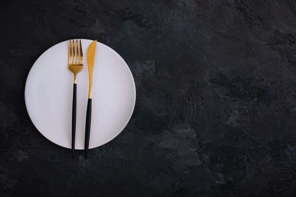 Empty plate with fork and knife on dark stone background. Gold and black tableware with white plate
