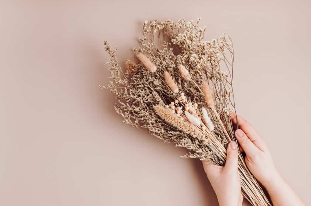 Woman composing bouquet of dry flowers and herbs